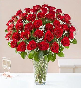 /three dozen roses in glass vase