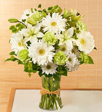 green and white arrangement in gathering vase